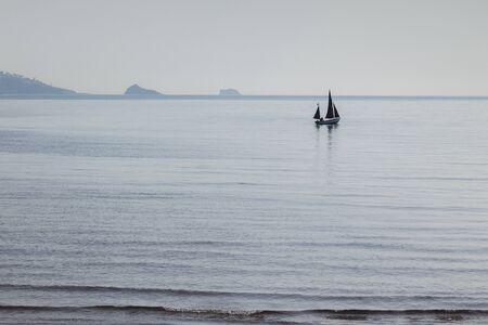 Distant Sailing Boat Torbay UK Archivio Fotografico