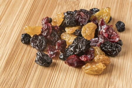 Mixed Dried Fruit, with Raisins, Cherries, Blueberries, Cranberries, on a Bamboo Board Archivio Fotografico - 134361465
