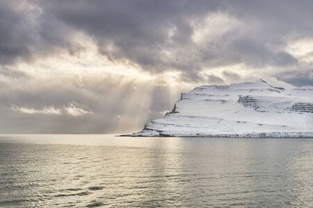 Beams of light on the sea in Iceland's East Fiords. Archivio Fotografico - 139748201