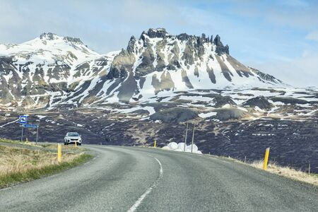 28 April 2018: South Iceland - Through the windscreen shot of the Iceland Ring Road in South Island, driving through snowy mountain scenery. Probably best at small sizes. Archivio Fotografico - 139748252