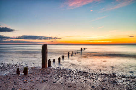 Remains of groynes on the beach at Sandsend, Whitby, North Yorkshire, at dawn Archivio Fotografico