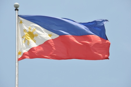 philippine: Flying national flag of the philippines at Rizal, Luneta Park in Manila, Philippines, isolated against a light blue sky. Stock Photo