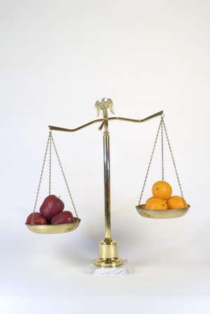 Latón balanza de la justicia que muestra la comparación de manzanas con naranjas