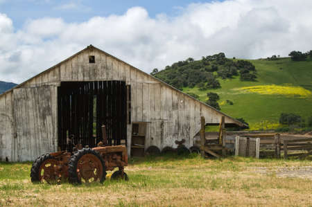 farm structure: Old wooden barn with rusted tractor sitting out front. Stock Photo