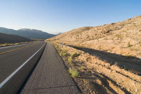 lonliness: Lonley aslphalt desert highway disappearing off into mountains.