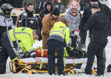 snowmobile: Levi Whiticker, on the stretcher, clasps hands for a moment with friend and fellow freerider Jessie Malmstein as EMS workers prepare to transport him to Central Vermont Hospital to have his condition and any potential injuries caused when he crashed follo