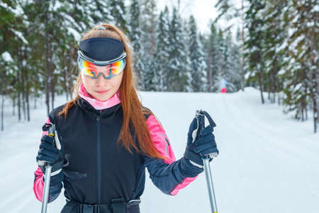 Female on the professional cross-country skiing with ski poles in the sports glasses