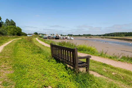 A solitary bench on the bank of a river with a clear view down river and of the nearby boatyard. A place to think and think