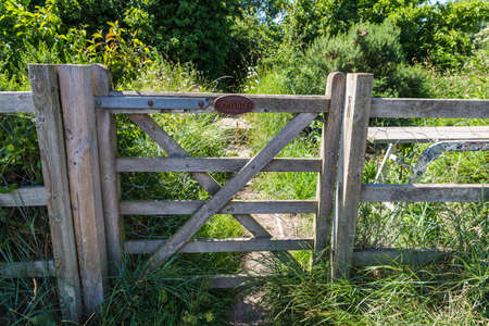 Private farm land fenced off by a large gate with a private keep out sign showing no access to the rural pathway