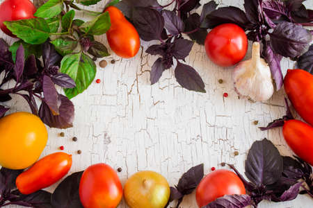 craquelure: Old white background with tomatoes and basil arranged in a circl
