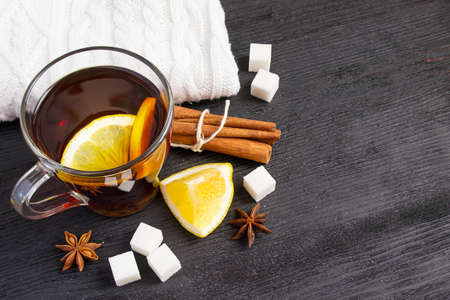 cosiness: Cup of tea with lemon, cinnamon, knitted rug. Winter charming still life, with space for text Stock Photo