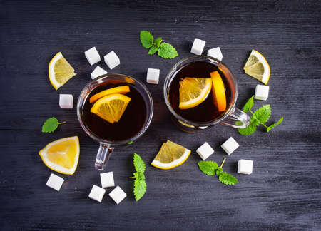 cosiness: Black tea with lemon and sugar on a dark background, top view