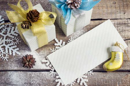 congratulatory: Congratulatory Letter, Christmas gifts, snowflakes, Christmas toys and bumps on the old wooden background, image tinted