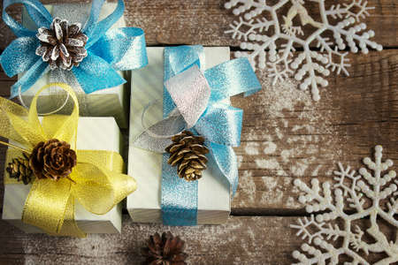 festively: Boxes with gifts festively decorated with shiny bows and fir cones on old wooden background