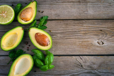 Food background with avocado, lime, parsley and basil on old wooden boards. Top view, space for text. Stock Photo