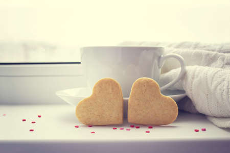 Two biscuits in the shape of a heart on a background with a cup of hot coffee on the window.