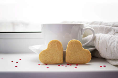 Two biscuits in the shape of a heart on a background with a cup of hot coffee and a blanket on the window.