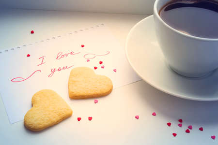 love shape: Cup of coffee, cookies in the shape of a heart and a declaration of love.