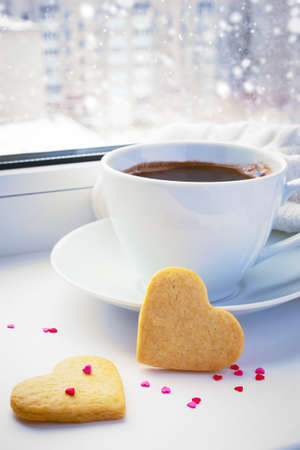 Winter snow-covered window, a cup of coffee and biscuits