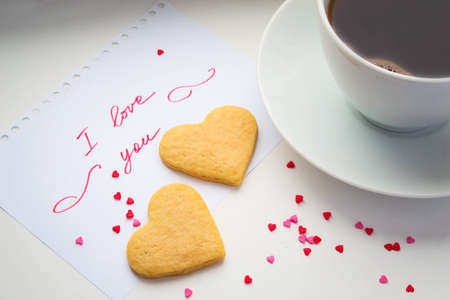 love shape: Declaration of love, a cup of coffee and cookies in the shape of a heart.