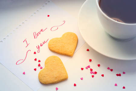 Declaration of love, a cup of coffee and cookies in the shape of a heart.
