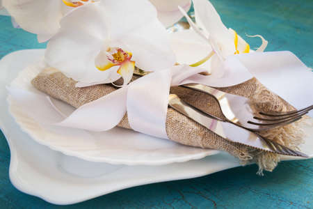craquelure: Spring table setting with White orchid decorations and napkins on a turquoise craquelure background