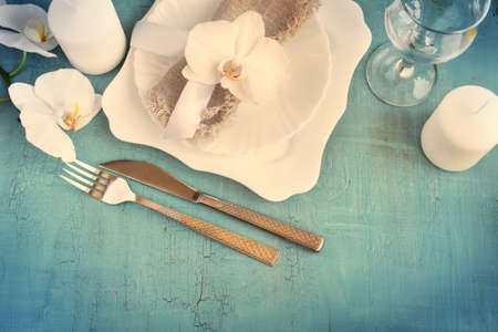craquelure: Vintage table setting with orchid decorations, candles, wineglass on a blue background. Top view. Tinted. Space for text