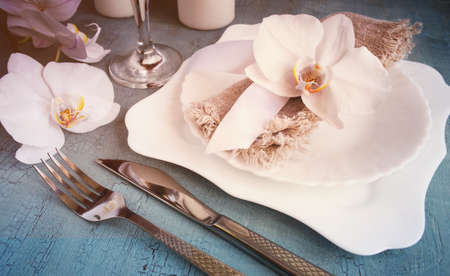 craquelure: Vintage table setting with orchid decorations on a blue background. Tinted