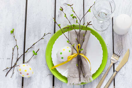 plate setting: Spring Easter Table setting at white wooden table.