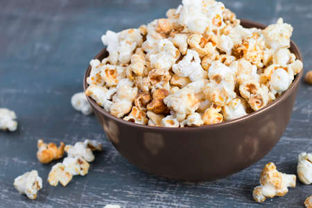 bowls of popcorn: Sweet caramel popcorn in a  bowl on a dark blue background, selective focus
