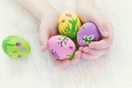 butterfly rabbit: Painted Easter eggs with spring pictures in a childs hands.
