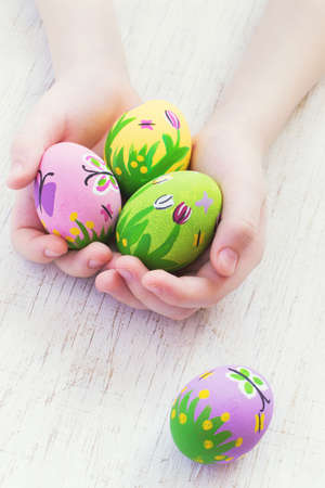 pink and green: Painted Easter eggs in the childrens hands. Stock Photo