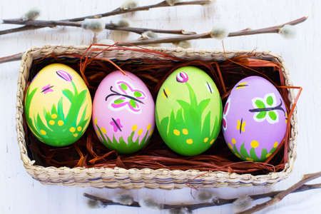 pink and green: Painted Easter eggs in a wicker box on a white background Stock Photo