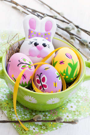 butterfly rabbit: Easter composition with colored eggs and rabbit on a white background