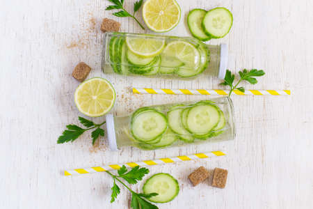 infusing: Lime, cucumber, parsley lemonade in bottles on a white background
