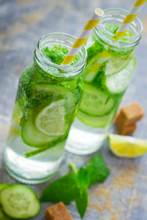 infusing: lime and cucumber detox drink, selective focus. Stock Photo