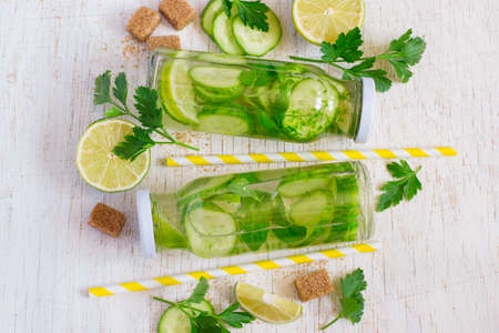 infusing: Bottles with homemade cucumber lime lemonade on a white background Stock Photo
