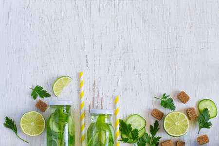 limonada: Antecedentes botellas de limonada casera, pepino, lima y azúcar moreno Foto de archivo
