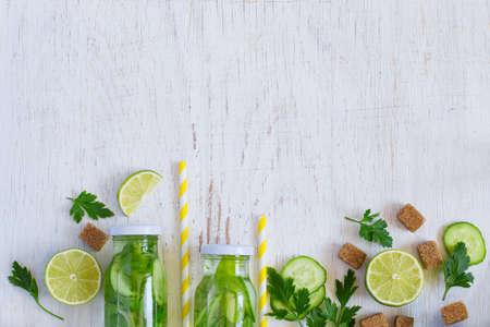 Background homemade lemonade bottles, cucumber, lime and brown sugar