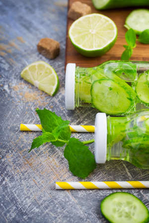 infusing: Lime cucumber lemonade and ingredients on a gray vintage background