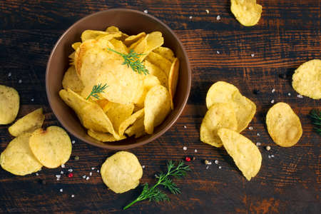Potato chips with greens in a bowl, top view. Stock Photo