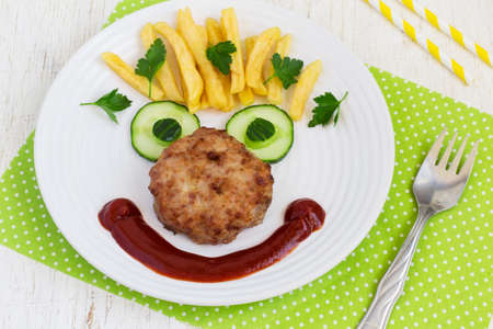 Funny food face with a chop, French fries and cucumber. Stock Photo