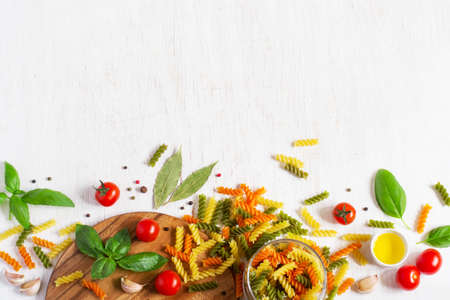 Background with colored paste, cherry tomatoes, spices. The top view, space for text