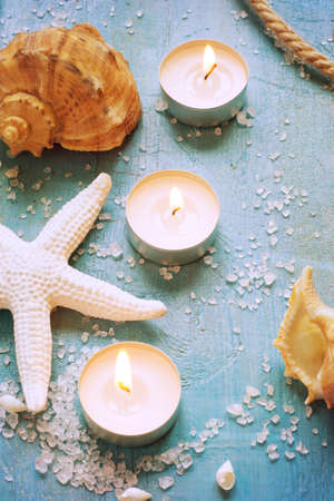 craquelure: Burning candles and marine items on a turquoise background, tinted Stock Photo