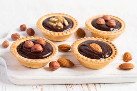 nutty: Nutty dessert - small tarts with different nuts and chocolate. Stock Photo