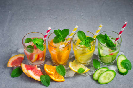infusing: Refreshing summer drinks water with ice and lemon, orange, grapefruit and cucumber Stock Photo