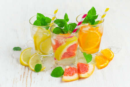 infusing: Refreshing summer drinks water with ice and lemon, orange  and  grapefruit Stock Photo