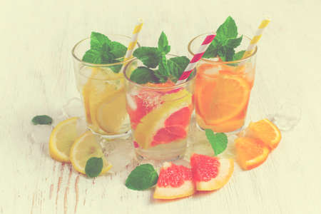 infusing: Refreshing summer drinks water with ice and lemon, orange  and  grapefruit, tinted Stock Photo