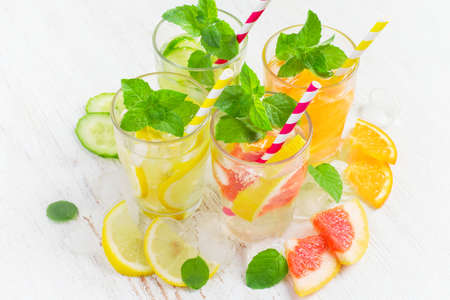 infusing: Summer drinks with ice, mint and citrus. Infused water in glass.