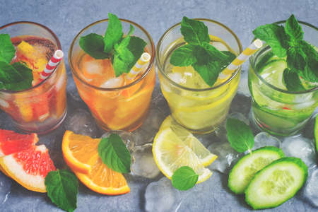 infusing: Refreshing summer drinks water with ice and lemon, orange, grapefruit and cucumber, tinted